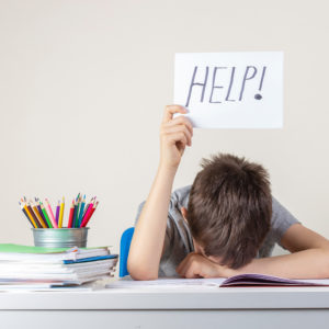 """Child working on homework puts up a sign with the word """"HELP!"""" written on it."""